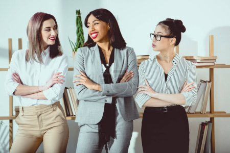 smiling multiethnic businesswomen in formal wear standing with arms crossed