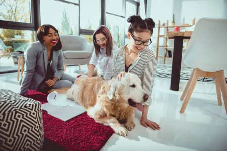 happy multiethnic businesswomen petting furry dog while sitting on the floor at office