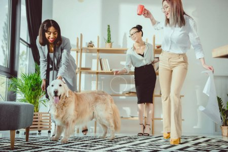 happy multiethnic businesswomen fooling around with dog at office