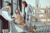 smiling multiethnic businesswomen in formal wear playing with dog at office