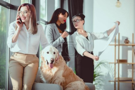 businesswoman talking on smartphone while petting dog during work at office