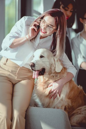 smiling caucasian businesswoman talking on smartphone and hugging dog