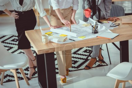 Photo for Cropped shot of architects in formal wear working with blueprints at table - Royalty Free Image