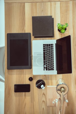 top view of laptop with graphics tablet and smartphone on wooden tabletop at office