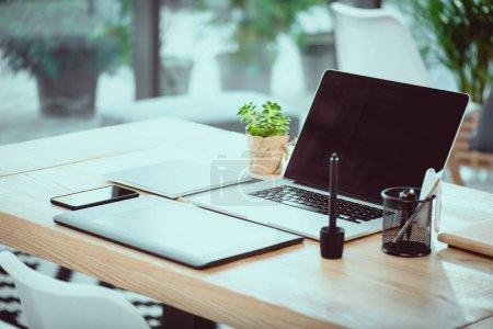 Photo pour Ordinateur portable avec blanc écran et tablette graphique avec smartphone sur une table en bois au bureau - image libre de droit