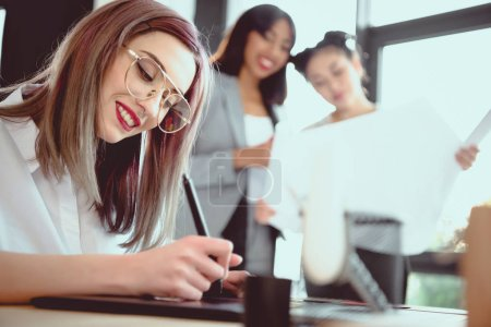 Photo for Young designer drawing on graphics tablet while her colleagues looking at blueprint - Royalty Free Image