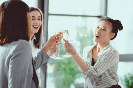 happy multiethnic businesswomen clinking with champagne glasses and smiling