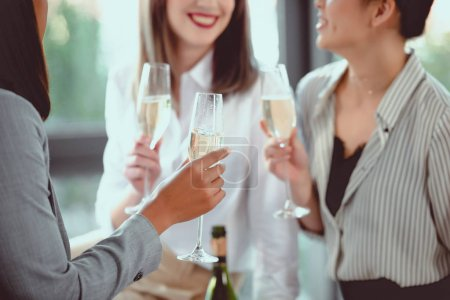 cropped shot of businesswomen in formal wear drinking champagne indoors