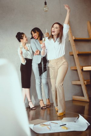 jeunes femmes d'affaires multiethniques célébrer les succès et buvant du champagne à l'intérieur