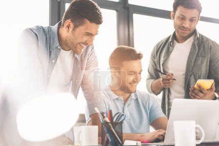 smiling young multiethnic businessmen using laptop and taking notes in office