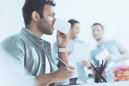 Photo for Side view of young businessman drinking coffee and colleagues standing behind in office - Royalty Free Image