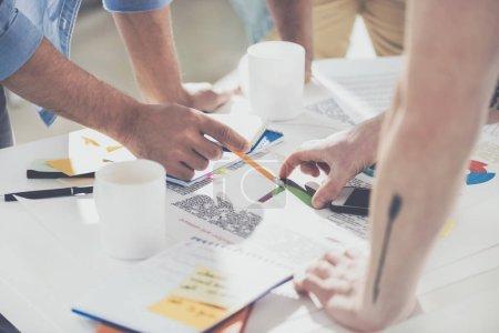 Photo pour Plan recadré d'hommes d'affaires pointant vers des diagrammes et travaillant sur un nouveau projet au bureau - image libre de droit