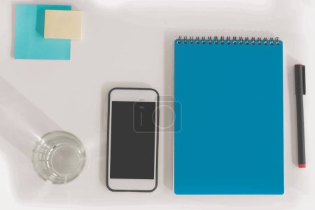 Top view of smartphone with blank screen, notebook with pen, glass of water and sticky notes