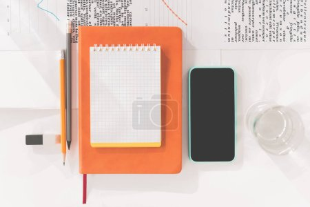 Top view of smartphone with blank screen, notebooks and pencils at workplace
