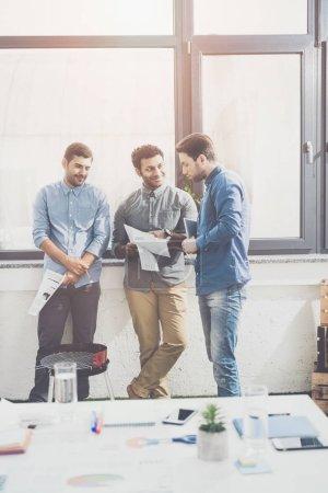 Foto de Tres jóvenes empresarios Unidos y discutir artículos, concepto de negocio trabajo en equipo - Imagen libre de derechos