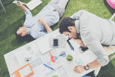 Young businessmen sleeping on the table and green grass carpet at modern office, business teamwork
