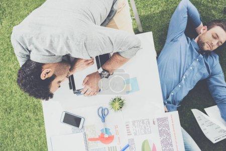 Jeunes hommes d'affaires, dormir sur la table et un tapis d'herbe verte au bureau moderne, travail d'équipe affaires