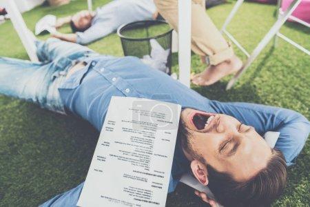Young businessmen sleeping on green grass carpet at modern office, business teamwork