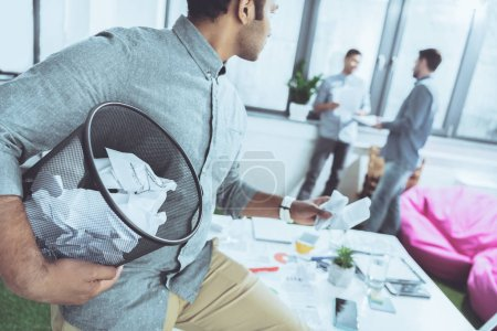 Photo pour Homme d'affaires détenant le bac à ordures avec papiers et regardant des collègues de travail, travail d'équipe entreprise - image libre de droit