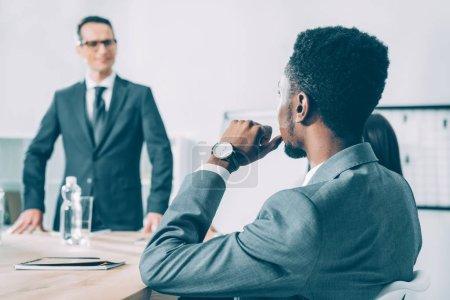 african american businessman listening to caucasian boss during conversation