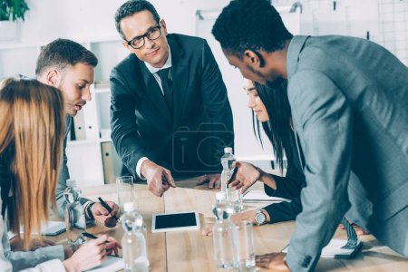 Photo for Multiracial businesspeople having conversation in conference hall and looking at tablet - Royalty Free Image