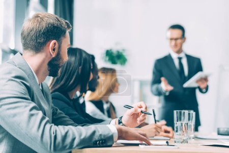 successful multiracial businesspeople having conversation in conference hall