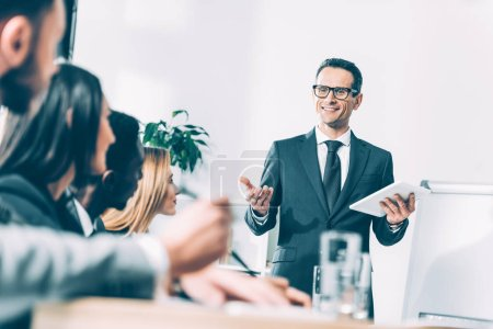 Photo for Happy handsome team leader with tablet talking to multiracial managers in conference hall - Royalty Free Image