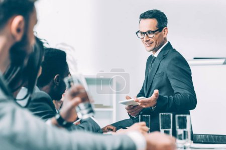 Photo for Handsome middle aged businessman talking to multiracial partners at conference hall - Royalty Free Image