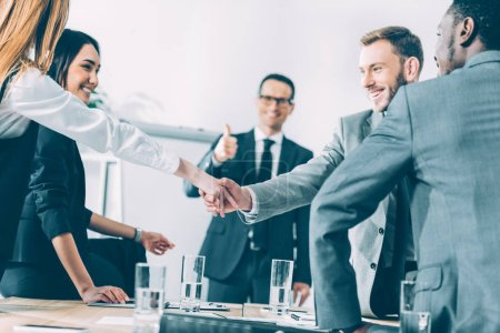 Photo for Multicultural businesspeople shaking hands in conference hall while team leader showing thumb up - Royalty Free Image