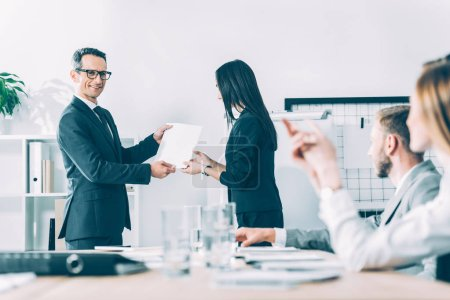boss rewarding asian manageress at modern office
