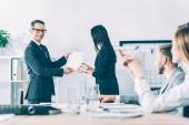 boss rewarding asian manageress at modern office