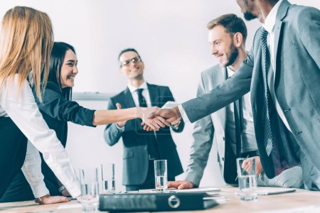 multicultural businesspeople shaking hands in conference hall