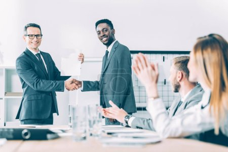 caucasian boss shaking hand of african american manager while colleagues clapping