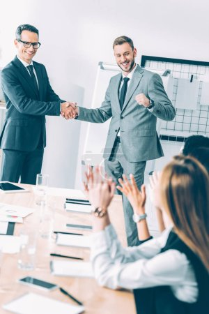 boss shaking hand of manager while colleagues clapping at table