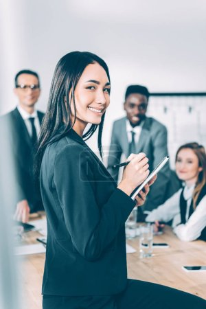 asian businesswoman with notebook in conference hall with blurred multicultural colleagues on background