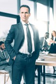 handsome businessman in suit with hands in pockets