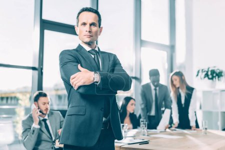 handsome businessman looking at camera with crossed arms in conference hall