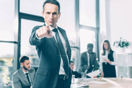 serious businessman pointing at camera in conference hall with blurred colleagues on background