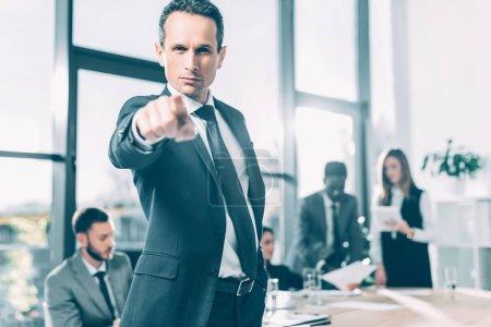 Photo pour Homme d'affaires grave, pointant à la caméra dans la salle de conférence avec des collègues floues sur fond - image libre de droit