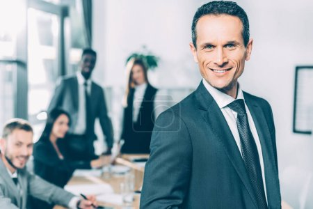 handsome businessman looking at camera in conference hall with multiracial partners blurred on background