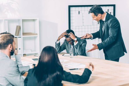 caucasian boss abusing on african american manager in conference hall with his colleagues