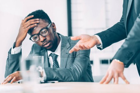 partial view of exhausted african american businessman listening to boss