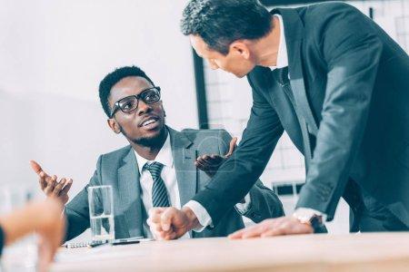 multiethnic businessmen having conversation at office