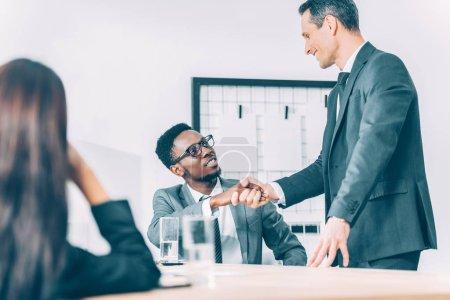 Photo pour Beaux hommes d'affaires multiethniques serrant la main dans le bureau moderne - image libre de droit