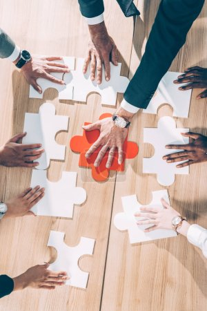 overhead view of multiracial businesspeople assembling puzzle on table