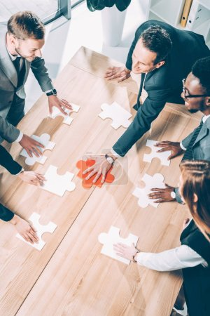 high angle view of multiracial businesspeople assembling puzzle on conference table