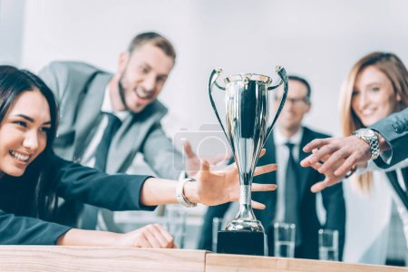 Photo for Close-up shot of multiracial businesspeople trying to catch champion cup - Royalty Free Image