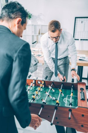 handsome businessmen playing table football in modern office