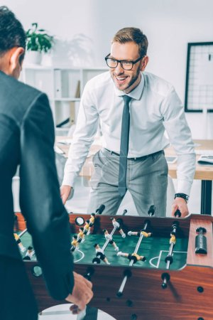 businessmen playing table football in modern office