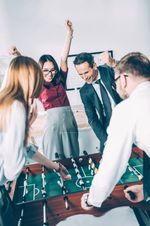 group of multiethnic businesspeople playing table football in modern office